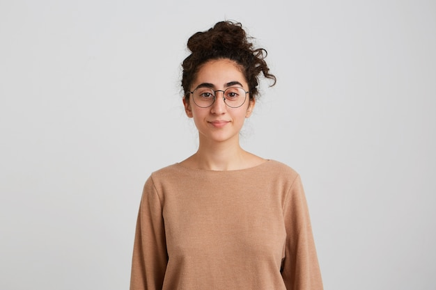 Estudiante bastante joven confiada con moño de pelo oscuro y rizado viste jersey beige y gafas se siente tranquilo y mira al frente aislado sobre una pared blanca luciendo serio y tranquilo
