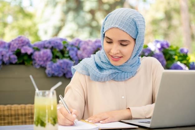 Estudiante bastante musulmán en hijab tomando notas en el cuaderno mientras está sentado frente a la computadora portátil mientras trabaja en un proyecto al aire libre