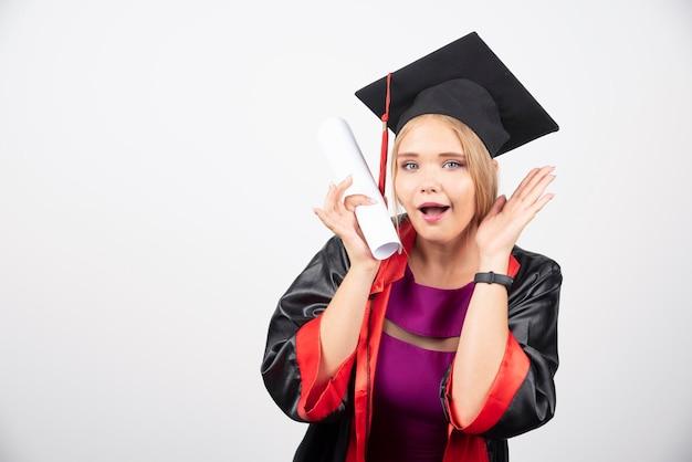 Estudiante en bata recibió diploma sobre fondo blanco. foto de alta calidad