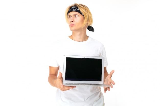 Estudiante en una bondana y una camiseta blanca sobre un fondo aislado en el estudio sosteniendo una computadora portátil con una pantalla en blanco, mirando a la izquierda
