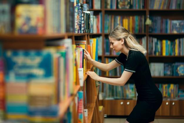 Estudiante buscando libros en una biblioteca