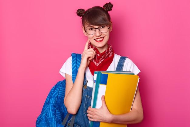 Estudiante de cabello oscuro con bolsa azul, sostiene una carpeta de papel de colores, sonríe, mantiene el dedo índice en su mejilla. jovencita usa camiseta, overol de mezclilla con pañuelo rojo en el cuello. adolescente vuelve a la escuela.