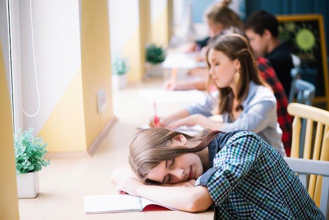 Estudiante cansado durmiendo en la libreta