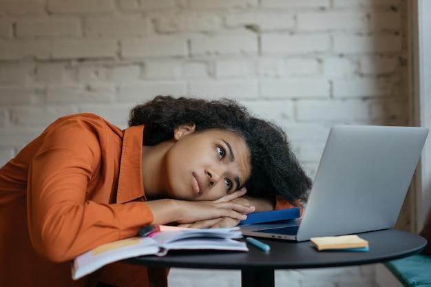 Estudiante cansado durmiendo en libros, exceso de trabajo. mujer agotada después de trabajar duro, multitarea. frustrado, triste freelancer no cumplió plazo