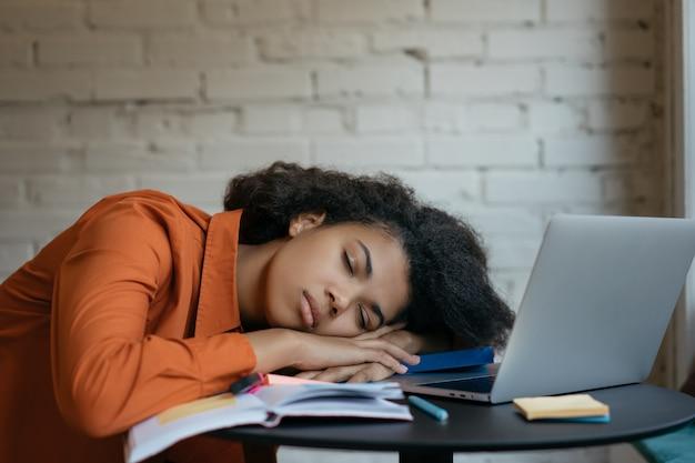 Estudiante cansado que duerme en los libros en la biblioteca, trabajador, concepto con exceso de trabajo
