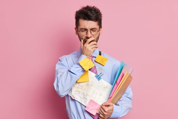 Estudiante cansado tiene expresión somnolienta cubre la boca con la mano y bosteza vestido con ropa formal se prepara para poses de exámenes
