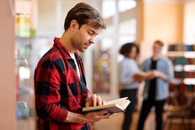 Estudiante casual con libro mirando a través de tareas o texto antes de la lección o examen en la biblioteca de la universidad