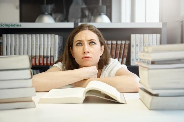 Estudiante caucásica enojada con cejas tensas mirando hacia arriba, tratando de prepararse para los exámenes y leer un manual, con una mirada cansada y frustrada contra la biblioteca de la universidad