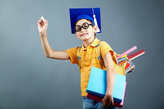 Estudiante cestudiante con un trozo de tiza y sujetando libros pesadoson un trozo de tiza y sujetando archivadores pesados