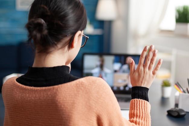 Estudiante charlando con un colega universitario durante el seminario web en línea usando una computadora portátil, mujer joven que tiene educación remota durante la cuarentena de coronavirus mientras está sentada en la sala de estar