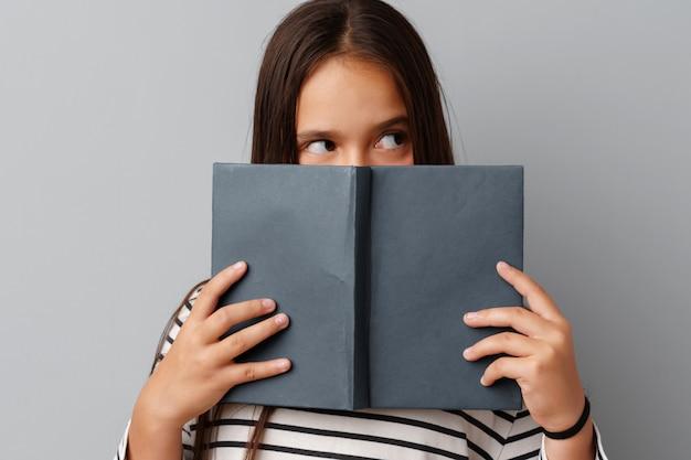 Estudiante chica adolescente sosteniendo un libro en sus manos sobre un gris