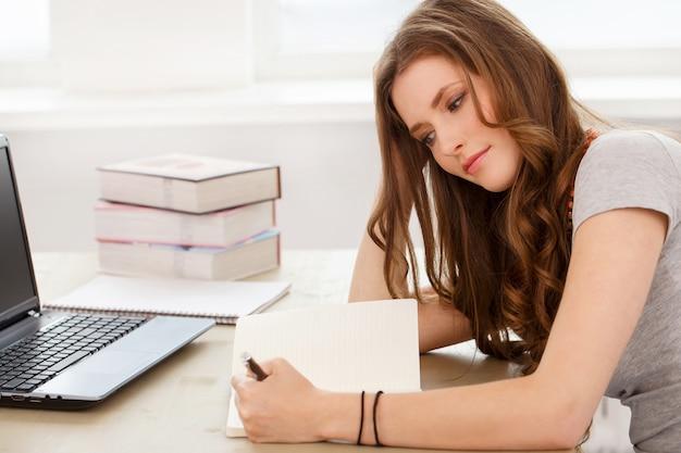 Estudiante. chica atractiva junto a la mesa