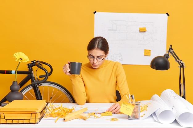 Estudiante concentrada de la facultad de arquitectura hace la tarea, piensa en ideas creativas, bebe café, se sienta en un espacio de coworking, crea bocetos y planos, desarrolla su propio espíritu empresarial social
