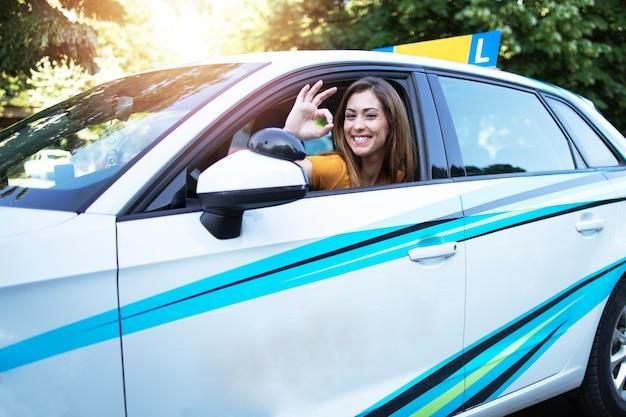 Estudiante de conducción de automóviles que muestra un signo de gesto bien y sentado en la posición del conductor del vehículo