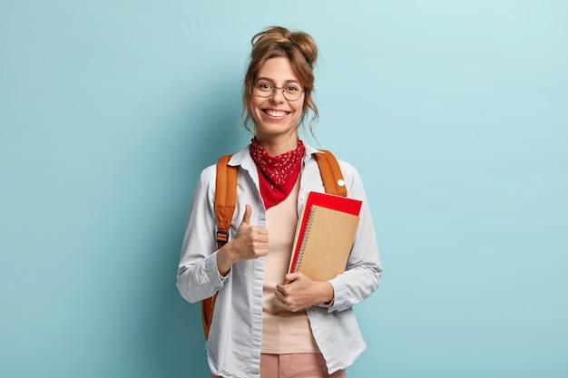 El estudiante contento da su aprobación, mantiene el pulgar en alto, sostiene el cuaderno y el diario, tiene una sonrisa feliz, dice que está bien, usa anteojos ópticos