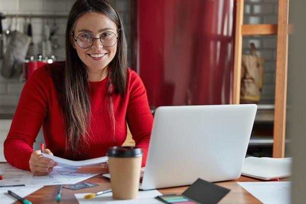 El estudiante contento se prepara para el seminario, escribe la tarea, verifica la documentación del texto, usa una computadora portátil, se sienta en la mesa de la cocina
