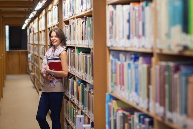 Estudiante contra la estantería en la biblioteca