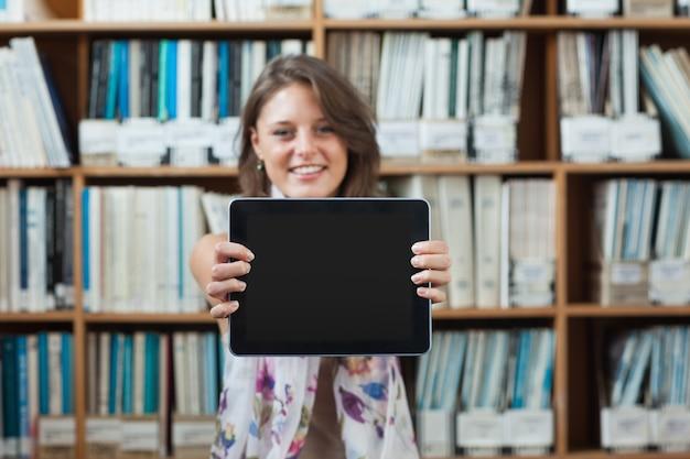 Estudiante contra estantería con tablet pc en la biblioteca