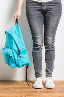 Estudiante de cultivo con mochila de pie sobre la mesa de madera