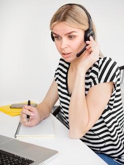Estudiante de cursos remotos en línea escuchando con auriculares