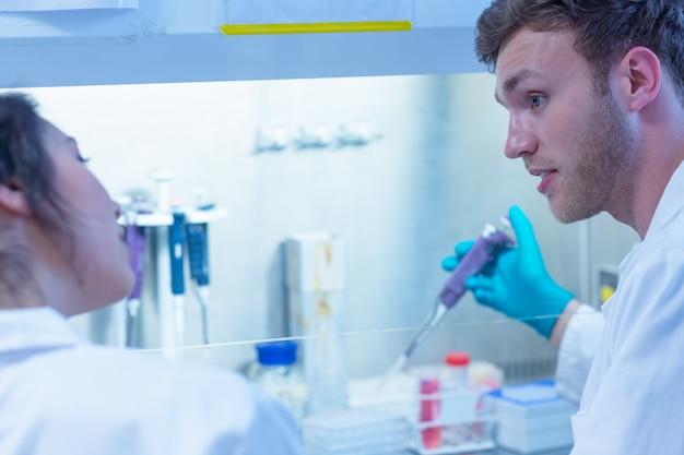 Estudiante de ciencias utilizando una pipeta en el laboratorio