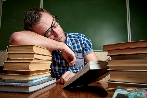 El estudiante desaliñado cansado y torturado en vidrios está durmiendo en la tabla en una pila de libros contra el fondo de la pizarra.