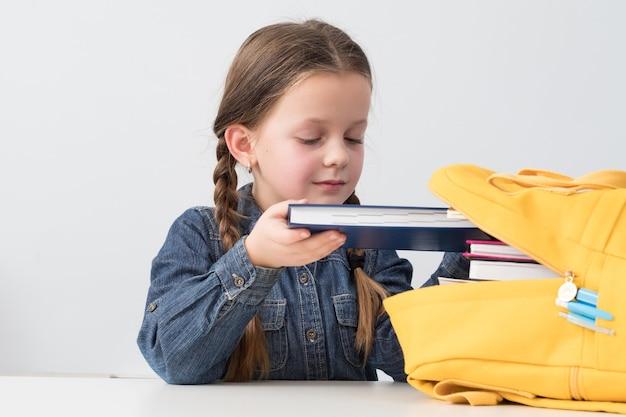 Estudiante diligente. niña de la escuela poniendo libros en mochila amarilla
