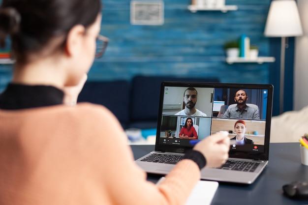 Estudiante discutiendo sobre educación universitaria mirando reunión en línea usando computadora portátil. mujer joven con educación remota sentada en la sala de estar durante la cuarentena por coronavirus