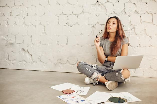 Estudiante de diseño de moda femenina pensando trabajando en una computadora portátil en un ambiente de estudio brillante.