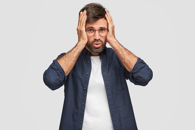 Estudiante disgustado estresante posando contra la pared blanca
