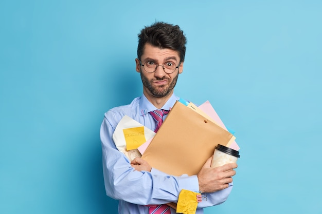 El estudiante disgustado y con exceso de trabajo trabaja duro antes de que la sesión de examen tenga una taza de café desechable y los papeles recuerden la fecha límite viste ropa formal