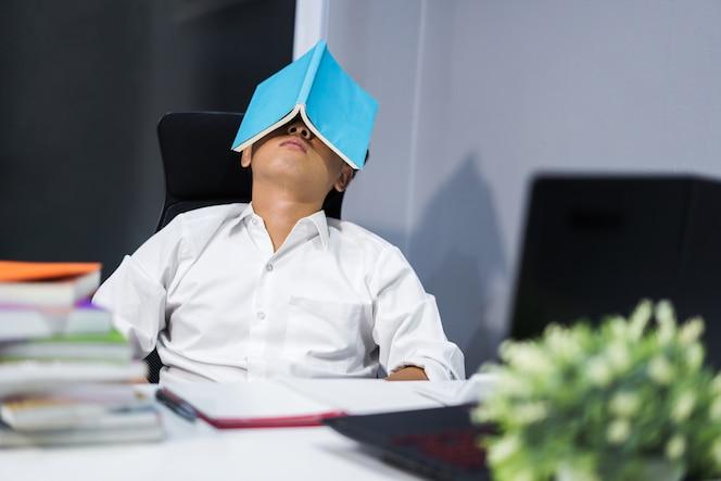 Estudiante dormido en el escritorio con el libro en la cara