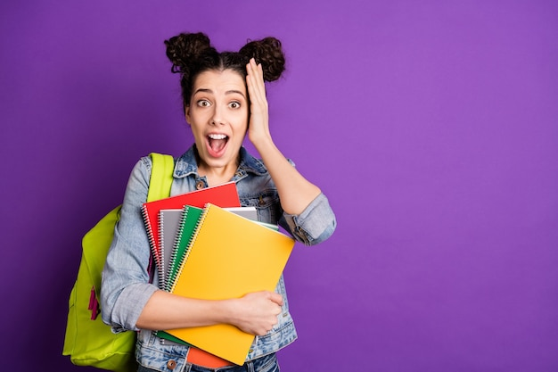 Estudiante elegante con cabello rizado posando contra la pared violeta