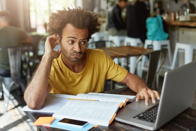 Estudiante elegante con peinado africano con aspecto dudoso mientras mira una computadora portátil sin comprender el nuevo material tratando de encontrar una buena explicación en internet
