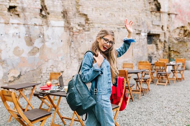 Estudiante encantador aprobó los exámenes a la perfección. adorable niña con un traje de mezclilla de moda sale del café al aire libre y se despide de sus amigos.