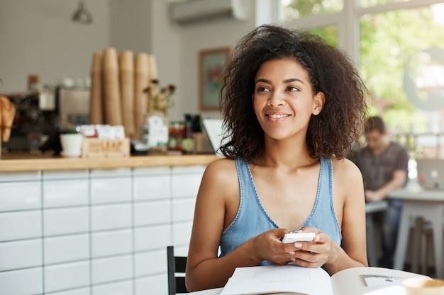 Estudiante de ensueño hermosa mujer sentada en la cafetería con libros y revistas sonriendo sosteniendo teléfono pensando.