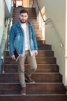 Estudiante en escaleras marrones. caucásico, sonriente, guapo, barbudo, hombre, con, mochila, cuadernos, en, reabrir, campus universitario, pasillo. freelancer en la oficina de coworking moderna.