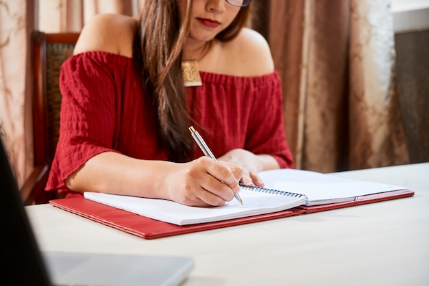 Estudiante escribiendo en libro de texto