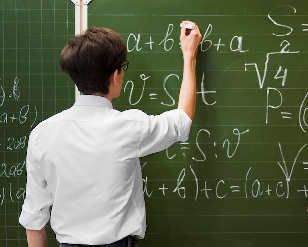 Estudiante escribiendo en pizarra