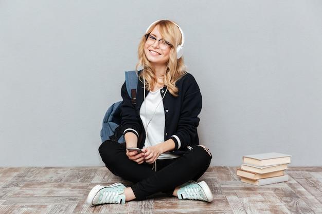 Estudiante escuchando música en el piso