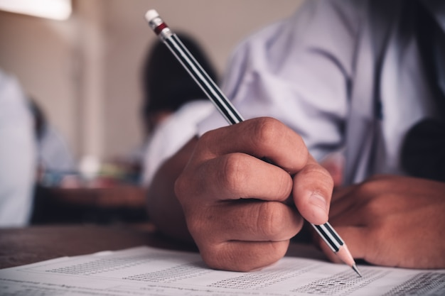 Estudiante de la escuela haciendo una prueba educativa con estrés en el aula