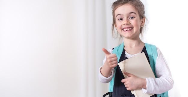 Estudiante de la escuela primaria de niña con una mochila y un libro sobre un fondo claro. el concepto de educación y escuela primaria. lugar para el texto.