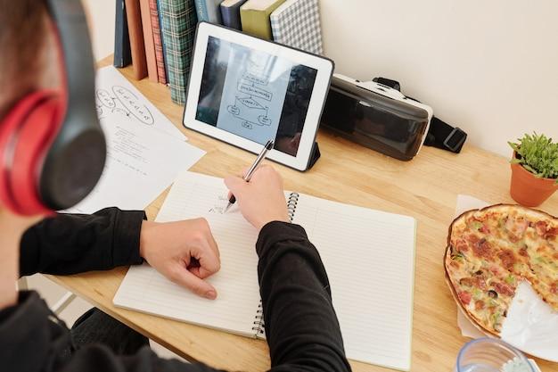 Estudiante de la escuela sentado en su escritorio en casa, viendo el curso de programación en línea y el esquema de dibujo en el libro de texto