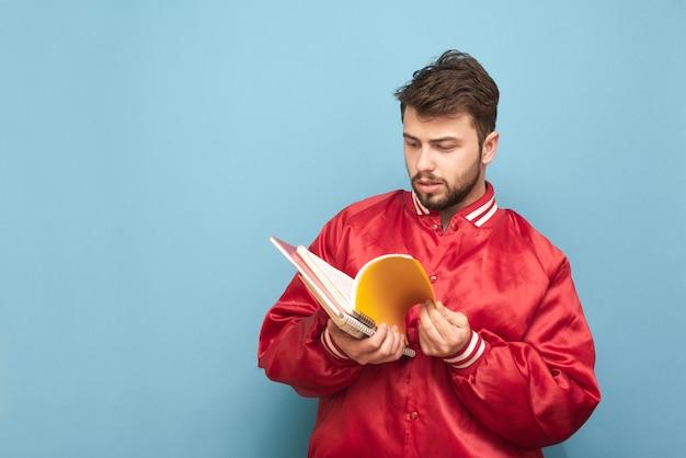 Estudiante estadounidense con barba de pie en azul con un cuaderno en la mano y lee