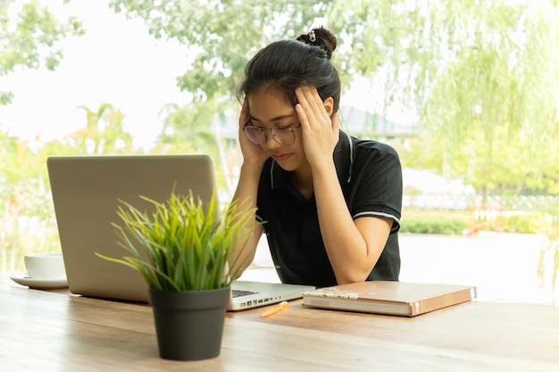 Estudiante estresado sintiendo dolor repentino después de mucho tiempo usando una computadora portátil para el estudio.