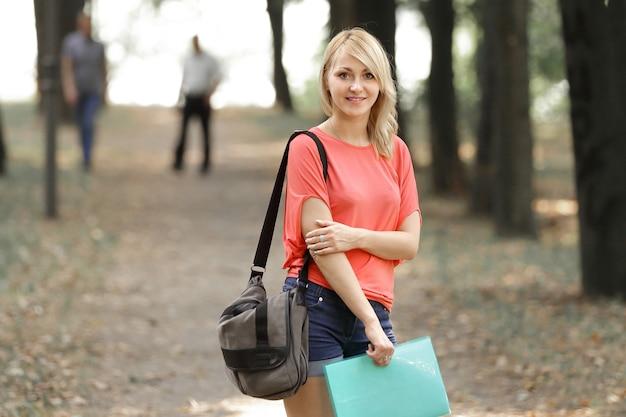 Estudiante exitosa con una bolsa y un portapapeles en el fondo del parque.