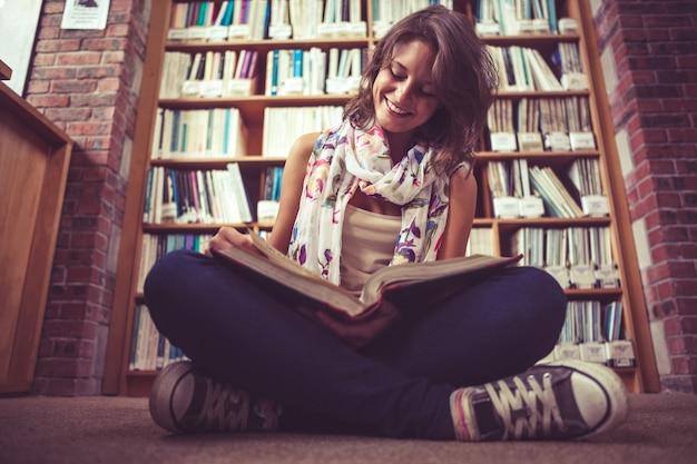 Estudiante feliz contra la estantería leyendo un libro en el piso de la biblioteca