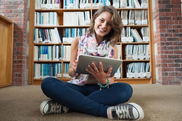Estudiante feliz contra estantería con tablet pc en el piso de la biblioteca