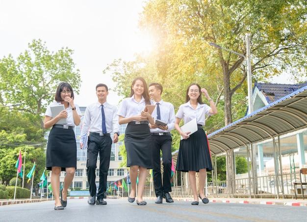 Estudiante feliz e inteligente caminando en la carretera