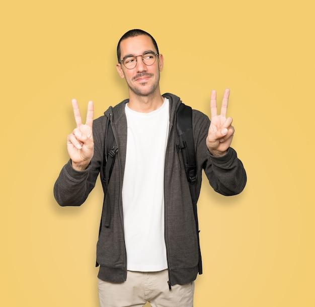 Estudiante feliz haciendo un gesto de victoria con los dedos